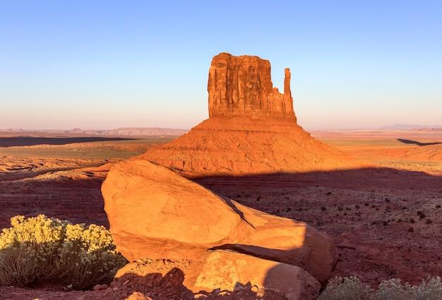 アメリカ合衆国、アリゾナ州とユタ州の国境にある有名なモニュメントバレーのビュートに沈む美しい夕日