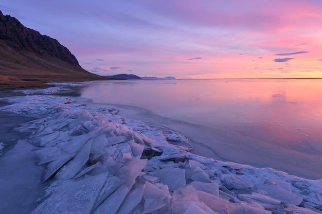 有名なダイヤモンドビーチに沈む美しい夕日、黒い砂のアイスランドビーチの流氷。ヨークルスアゥルロゥン、ダイアモンドビーチ、アイスランド