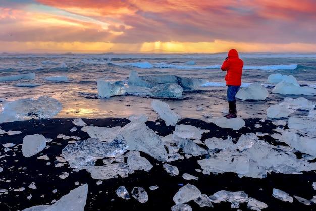 アイスランドの有名なダイアモンドビーチに沈む美しい夕日。この砂の溶岩のビーチは、アイスランド南東部の黒い砂のビーチがある氷河ラグーンのヨークルスアゥルロゥン氷の岩の近くに配置された、多くの巨大な氷の宝石でいっぱいです。