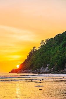 ビーチ、海、海、岩の周りの山に沈む美しい夕日