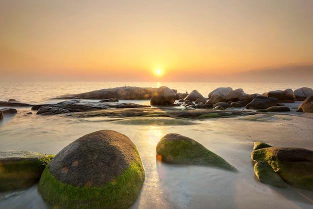 緑の苔で覆われた岩と海に沈む夕陽