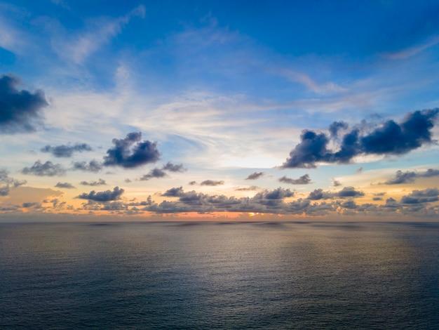 Красивый закат над морем моллюсков с фоном облака и неба. закат над тропическим пляжем. концепция лета природы. пик захода солнца над морем с желтым светом отражается в облаке.
