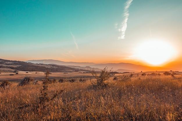 フィールドと山に沈む夕日