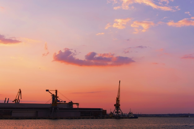 水に反射する太陽と郊外の都市の工業地帯に沈む夕日