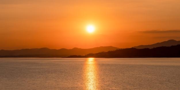 湖のほとりの山々に沈む美しい夕日。