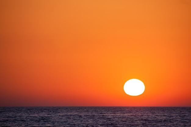 Красивый закат над морем с оранжевым небом.