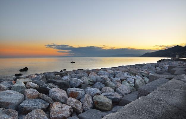 다채로운 돌의 틀이 있는 바다 위의 아름다운 일몰