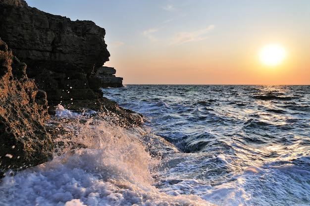 夏の日のクリミア半島の波状の嵐の黒い海の岩の多い海岸線に沈む美しい夕日
