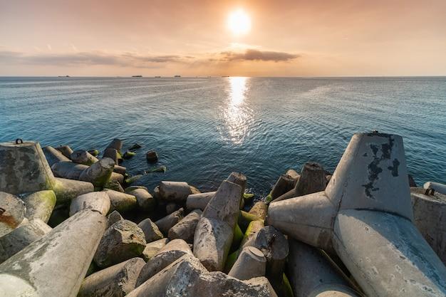 Красивый закат морской пейзаж. волнорезы четвероногие на берегу пирса