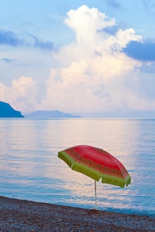 Beautiful sunset, shining sea surface and lonely sunshade on stony beach