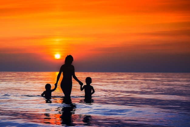 Beautiful at sunset silhouettes of mothers with children walking from the sea to the shore