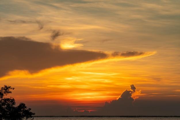 Красивое закатное небо над тропическим морем. золотое закатное небо. горизонт на море. красота в природе. вид на тропический пляж. живописный вид на закатное небо. слой красных и оранжевых облаков на небе.