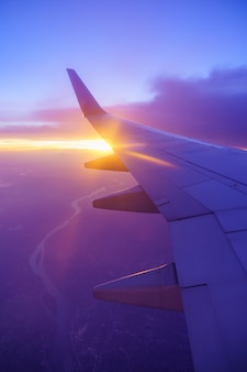 Beautiful sunset, sky on the top view, airplane flying view from inside window and cloud