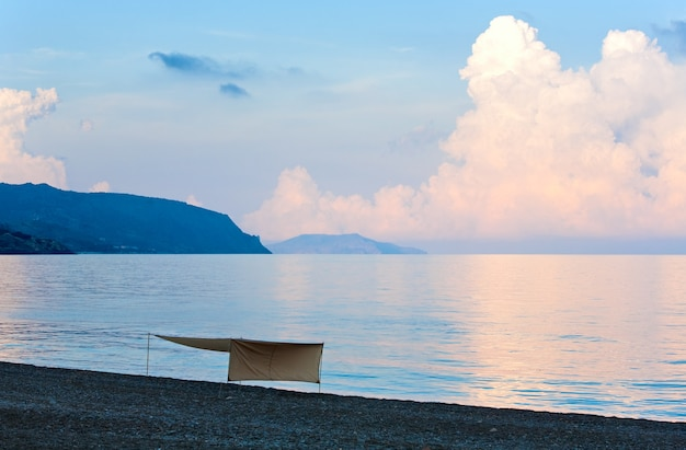 Beautiful sunset in soft pink-blue colors, shining sea surface and sunshade on beach