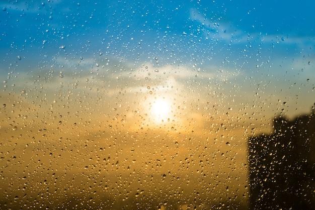 Красивый закат через забрызганное стекло с каплями дождя