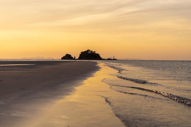 小さな波と美しい黄金の夕暮れの空とビーチから小さな島の美しいサンセットビュー。