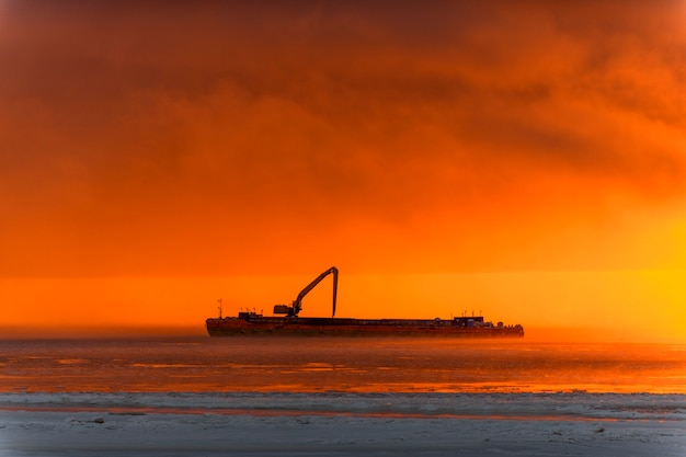 Beautiful sunset with fog in arctic sea. barge with excavator.