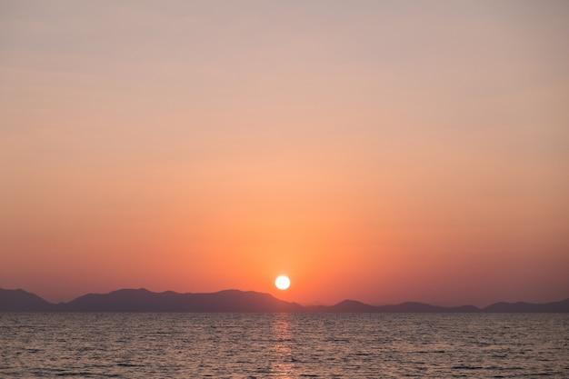 Beautiful sunset with a mountainous coastline on the horizon