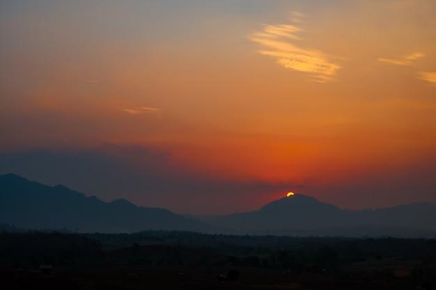 주황색 수평선으로 덮인 산들이 있는 아름다운 일몰.