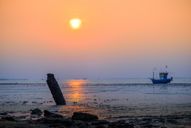 Beautiful sunset with old rusty fishing boat parked on a sandy beach