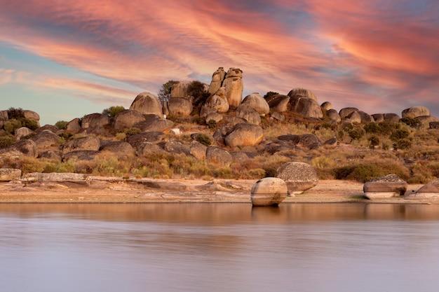 湖のほとりにオレンジ色の空と美しい夕日