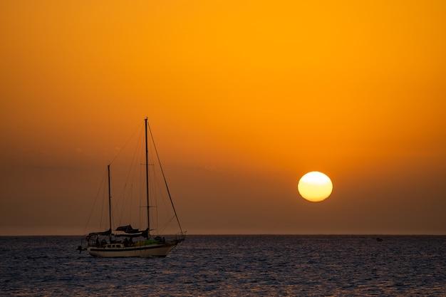Красивый закат с силуэтом парусника и солнечным диском, концепция путешествий и отдыха