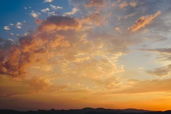 Beautiful sunset with the sun of orange tones behind the mountains and deep blue sky