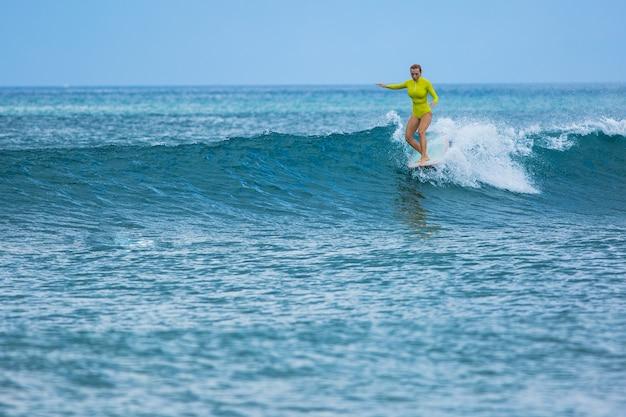 Bella ragazza surfista cavalca un longboard e fa un trucco per il nose ride.