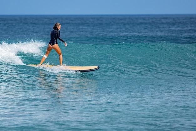 La bella ragazza del surfista cavalca una tavola da surf.
