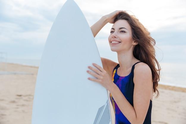 해변에서 서핑 보드와 함께 서 있는 아름 다운 서퍼 십 대 소녀