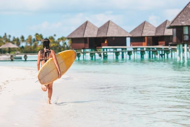 エキゾチックな休暇でスタンドアップパドルボードでターコイズブルーの海でサーフィンする準備ができて美しいサーファーの女性