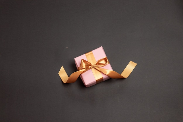 Beautiful surprise gift wrapped in pink paper with a gold ribbon bow on a dark background.