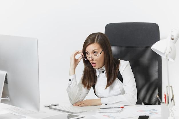 아름답고 분개한 갈색 머리 비즈니스 여성, 정장을 입고 안경을 쓰고 책상에 앉아 컴퓨터 작업을 하고 현대적인 모니터를 바라보며 가벼운 사무실에 문서를 가지고 있습니다.