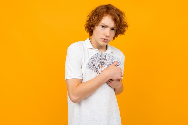 Beautiful surprised boy holds a fan of money notes in his hands on a yellow studio wall