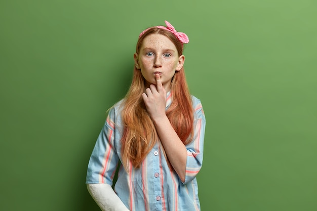 Beautiful surprised freckled girl keeps finger on rounded lips, has curious expression, listens something with interest, wears headband and shirt, has broken arm, isolated on green wall