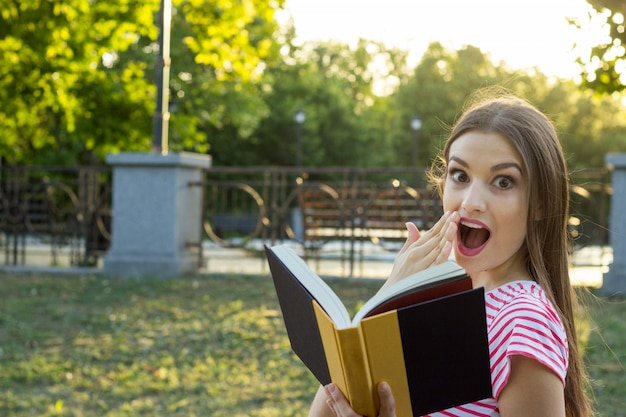 Beautiful surprised woman reading a book