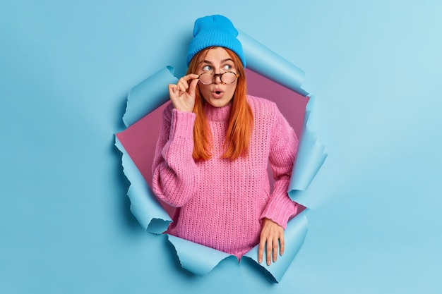 Beautiful surprised woman with red hair looks astonished through glasses concentrated aside wears hat and sweater notices incredible thing breaks through paper hole