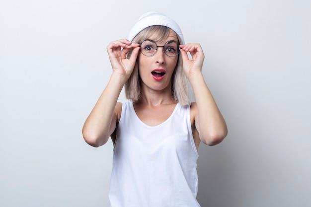 明るい背景に眼鏡をかけて美しい驚いた若いブロンドの女性。
