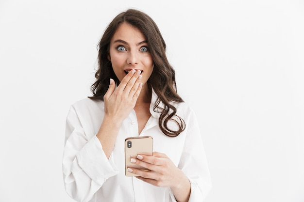 携帯電話を使用して、白い壁の上に孤立して立っている白いシャツを着て長い巻き毛のブルネットの髪を持つ美しい驚いた若い女性