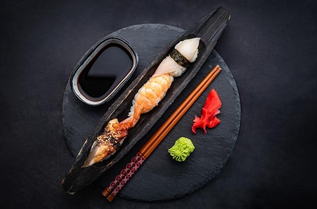 Красивая композиция из суши-сашими с креветками, имбирем и соевым соусом, подается с палочками для еды и ...