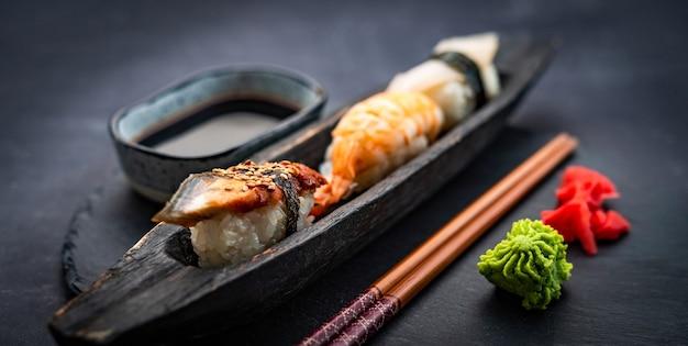 Красивый набор суши сашими с креветками, имбирем и соевым соусом, подается с палочками для еды и васаби на б ...