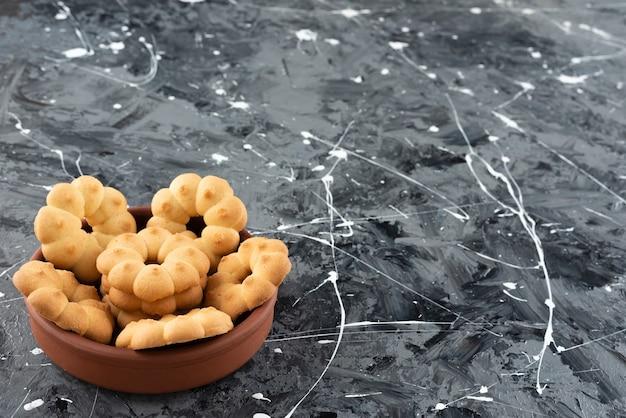 대리석 표면에 점토 그릇에 차를위한 아름다운 달콤한 쿠키