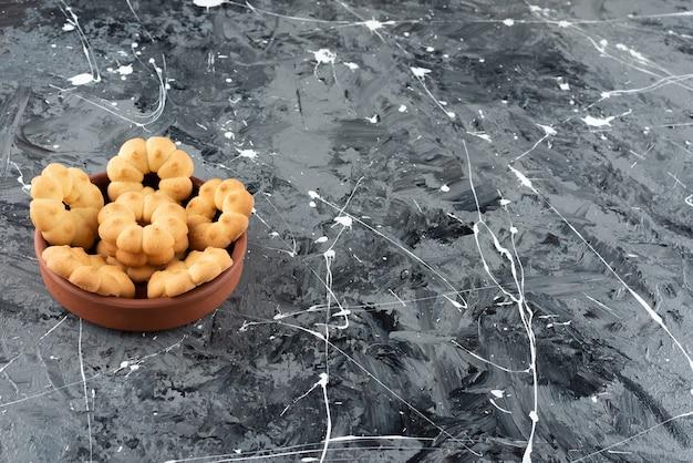 Bellissimi biscotti dolci per il tè in una ciotola di argilla su uno sfondo di marmo.