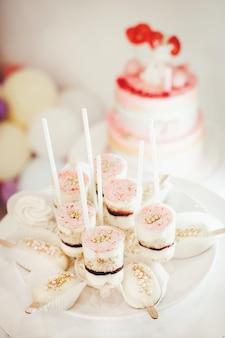 Красивый сладкий десерт на палочке на фоне именинного торта. вертикальное фото