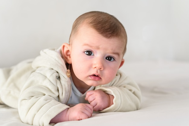 Beautiful and sweet newborn baby lying face down on the bed raising his head to look at the camera curiously.