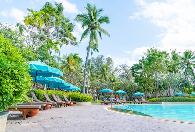 Beautiful swimming pool in hotel resort with umbrella and chair