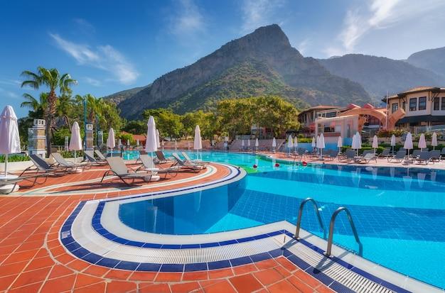 여름에 일출 시 일광욕용 침대와 우산이 있는 아름다운 수영장. 럭셔리 리조트. 리버티 호텔 리키아. 올루데니즈, 터키. 빈 수영장, 야외용 데크 의자, 푸른 나무, 산, 푸른 하늘이 있는 풍경