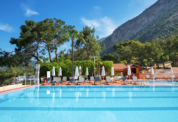 Красивый бассейн с шезлонгами и зонтиками на рассвете летом. роскошный курорт. либерти отели ликия. олюдениз, турция. пейзаж с пустым бассейном, шезлонгами, зелеными деревьями, горами, голубым небом