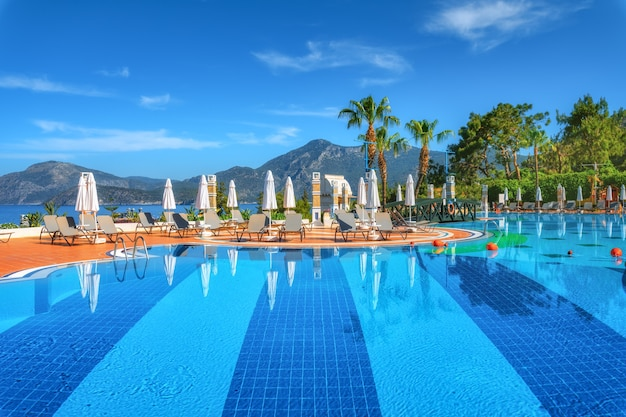 Beautiful swimming pool with sun beds and umbrellas at sunrise in summer. luxury resort. liberty hotels lykia. oludeniz, turkey. landscape with empty pool, deck chairs, green trees, mountain, blue sky