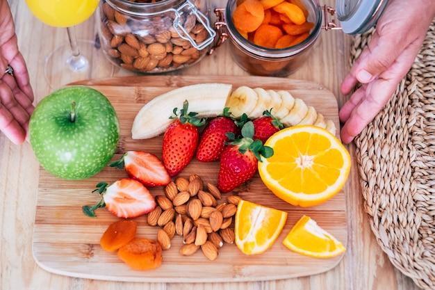 果物のような食べ物でいっぱいの美しいテーブルは、体重を減らして自分と一緒に過ごすために家でおいしい朝食をとることができます-テーブルにはバナナ、フランベリー、オレンジ、アップルなどがあります